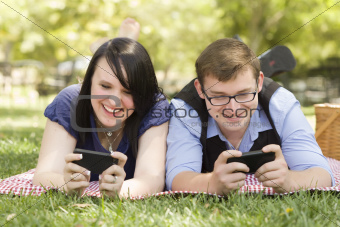 Attractive Young Couple at the Park Texting on Their Smart Phones Together.