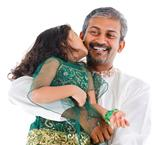 Happy Indian daughter kissing her father 