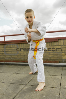 judoka teen boy training judo on the sky background