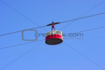 Cable car in mountains on blue sky background