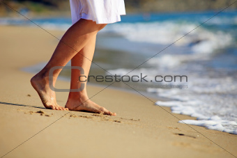 Cropped image of a young woman walking on a beach