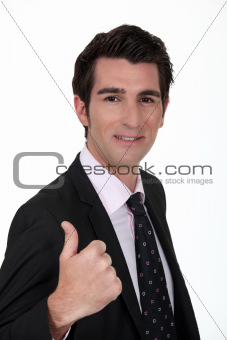 Smiling businessman giving the thumb's up