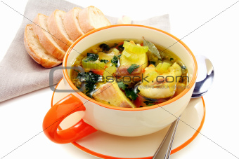 Fish soup with vegetables in bowl on a white background.