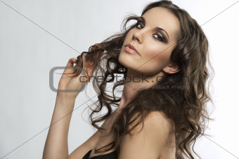 pretty brunette with curly hair with hand in the hair