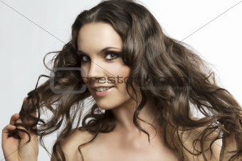 pretty brunette with curly hair, she's playing with hair