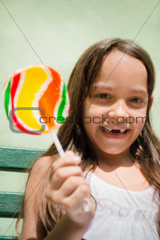 Portrait of pretty female child with lollipop smiling