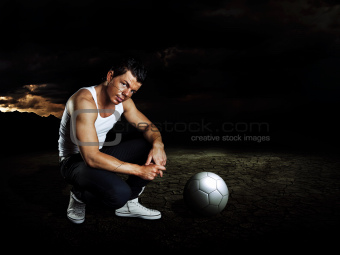 man with soccer ball staying on chapped soil