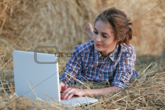 Country girl in lumberjack shirt with opened white laptop at haystack