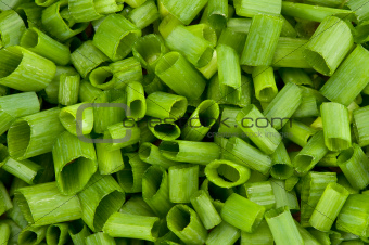 close up image of chopped spring onions on a white background