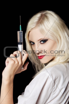 Smiling beautiful young girl in the image of nurse with syringe