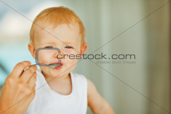 Portrait of eat smeared baby feeding by mom