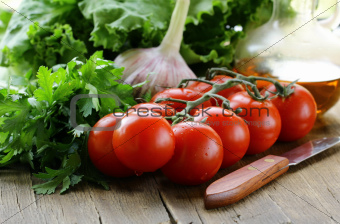 tomato, garlic, lettuce and oil on a wooden table