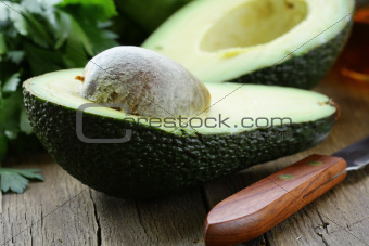 avocado cut in half on a wooden table