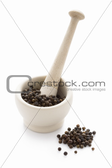 black peppercorns in a white pestle and mortar