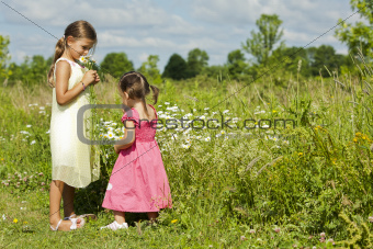 girls smelling flower