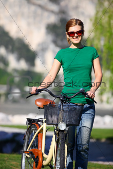 Portrait of a young Caucasian woman with her bike