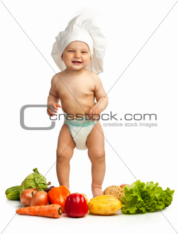 Little boy in chef's hat among fresh vegetables