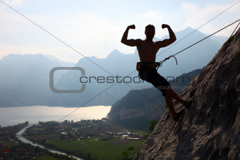 Silhouette of a rock climber flexing biceps