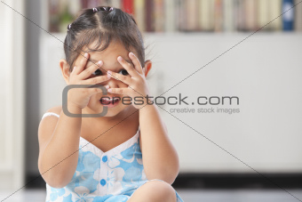 Little girl playing peekaboo