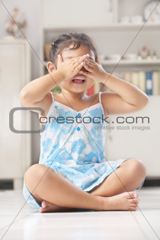 Little girl playing peekaboo or crying