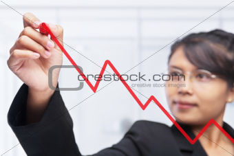 Asian businesswoman drawing graph with red felt tip pen