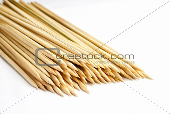 Multiple wooden bamboo skewers laying on white background