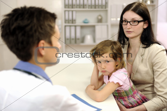 Pediatrician talking to mother and upset child