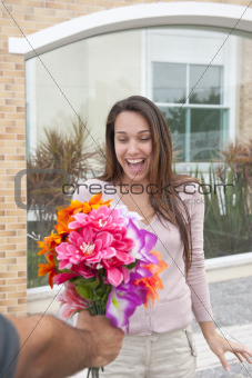 Man surprising his girlfriend with a bouquet