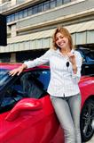 woman showing key of new red sports car