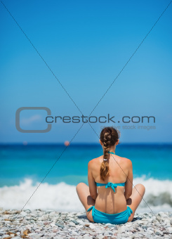 Woman sitting on sea shore. Rear view