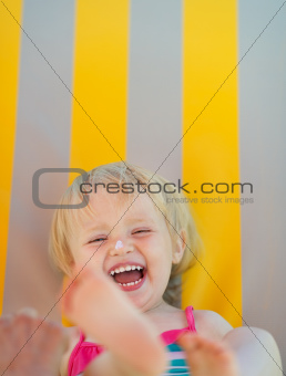 Portrait of laughing baby with sun block creme on nose