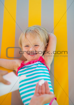 Baby waiting while mother applying sun block creme