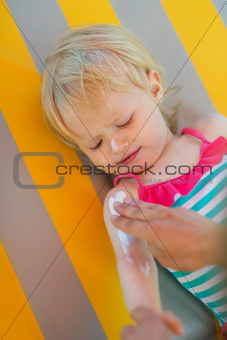 Baby waiting while mother applying sun block creme on arm