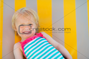 Portrait of happy baby laying on sun bed