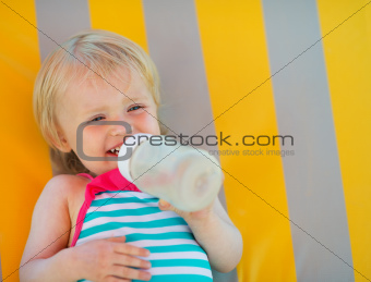 Portrait of happy baby laying on sunbed and drinking water