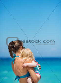 Mother with baby on sea shore looking into distance. Rear view