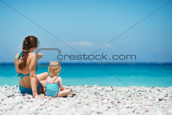 Mother sitting with baby on sea shore looking into distance. Rear view