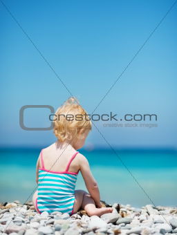 Baby sitting on sea shore. Rear view