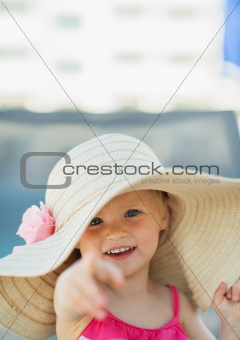 Portrait of baby in beach hat pointing in camera