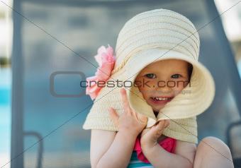 Portrait of baby hiding in big hat