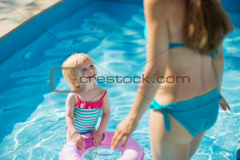 Baby standing in pool with inflatable ring and looking on mother
