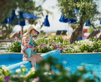 Mother with baby sitting in open air pool