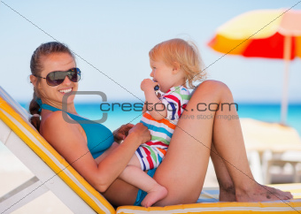 Portrait of happy mother and baby on sun bed