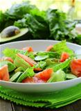 fresh salad with avocado and tomato on a wooden table