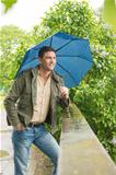 Man in park with blue umbrella