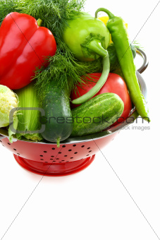 Fresh vegetables in metal colander.