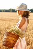 Beautiful woman with basket full of ripe spikelets of wheat in the field