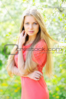 Portrait of beautiful woman in blooming tree in spring