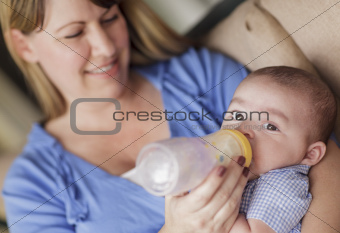 Happy Mother Bottle Feading Her Very Content Son.