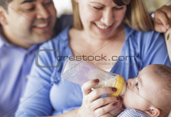 Happy Attractive Mixed Race Couple Bottle Feeding Thier Son.